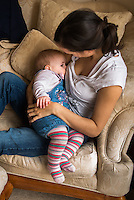 "A woman in her early twenties breastfeeding her nine month old baby girl at home while sitting on a sofa in her living room.<br /> <br /> Image from the breastfeeding collection of the ""We Do It In Public"" documentary photography picture library project: <br />  www.breastfeedinginpublic.co.uk<br /> <br /> <br /> Dorset, England, UK<br /> 08/03/2013<br /> <br /> © Paul Carter / wdiip.co.uk"