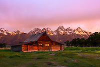 Moulton Barn at sunrise on Mormon Row against the Teton Range Mountains in Grand Teton National Park.