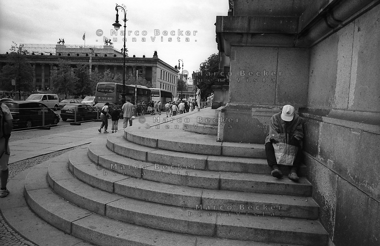 berlino, quartiere mitte. un mendicante sulla gradinata del duomo di berlino (berliner dom). l'altes museum sullo sfondo --- berlin, mitte district. a beggar on the steps of berlin cathedral (berliner dom). Altes Museum (Old Museum) on the background