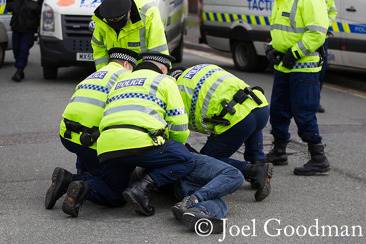 © Joel Goodman - 07973 332324 . 25/02/2012 . Hyde , UK . Police detain a man at the demonstration . The EDL demonstrate following an assault on Daniel Stringer-Prince, whose family say they do not want the demonstration to take place in the town in their son's name. The EDL say Daniel was assaulted by a gang of Asian men . At the same time , the BNP hold a rally in the town . Photo credit : Joel Goodman