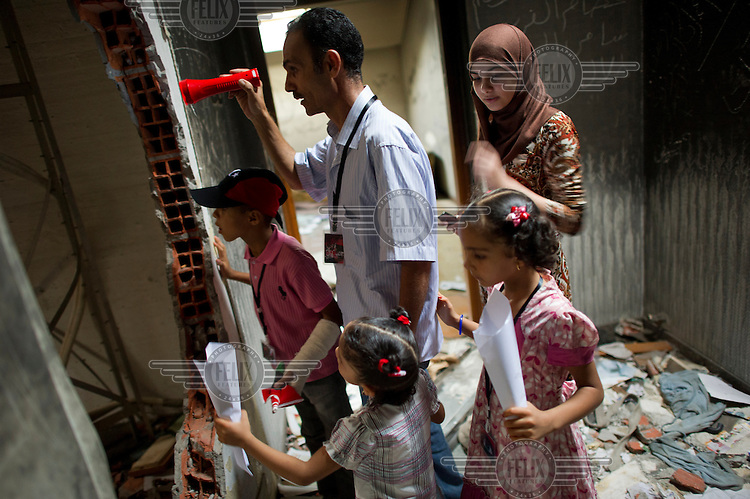 A man, his wife and children search through the Gadaffi compound and residence. After the fall of the regime these buildings were ransacked. Souvenir hunters visit the site to collect mementos. .