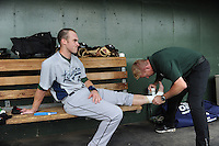 Infielder Zachary Johnson (8) of the Lexington Legends, has his ankle taped by trainer Steven Miller after twisting it in a game against the Greenville Drive on May 3, 2012, at Fluor Field at the West End in Greenville, South Carolina. (Tom Priddy/Four Seam Images)