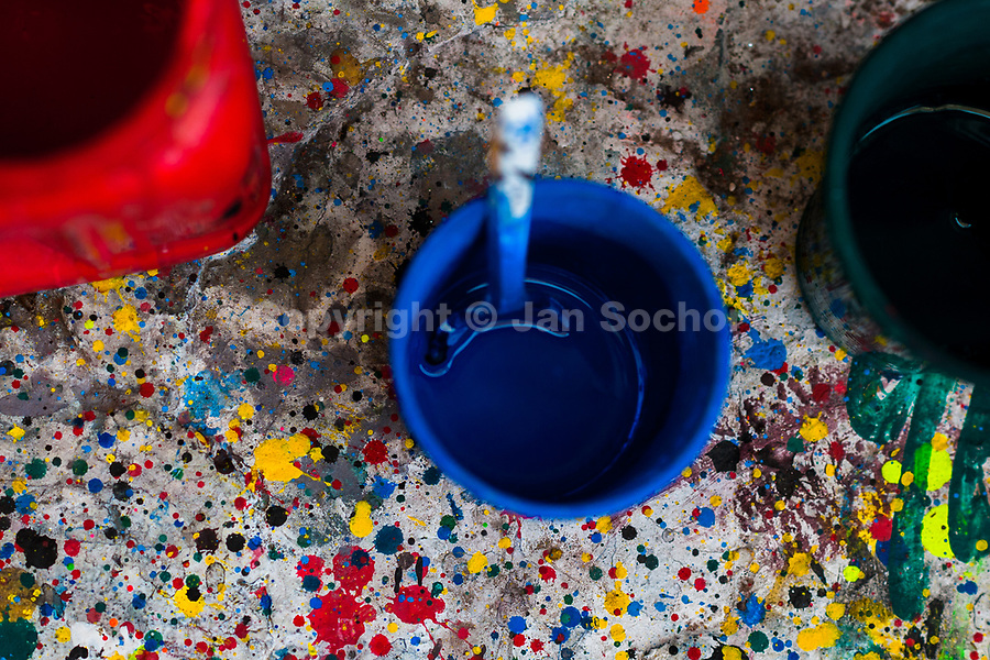 """Plastic cups filled with paint are seen placed on a splattered kerb in the sign painting workshop in Cartagena, Colombia, 13 April 2018. Hidden in the dark, narrow alleys of Bazurto market, a group of dozen young men gathered around José Corredor (""""Runner""""), the master painter, produce every day hundreds of hand-painted posters. Although the vast majority of the production is designed for a cheap visual promotion of popular Champeta music parties, held every weekend around the city, Runner and his apprentices also create other graphic design artworks, based on brush lettering technique. Using simple brushes and bright paints, the artisanal workshop keeps the traditional sign painting art alive."""