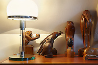 A Bauhaus-style table lamp beside teakwood sculptures of a falcon by the Dutch artist Jan Trapman, an owl by  J.A. Altorf, dated 1943 and a marabou by Van der Winkel, dated 1928