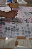 A Peace Boat volunteer writes a message of support for Ishinomaki residents after taking part in the clean-up operations in Ishinomaki, Miyagi Friday May 6th 2011. Around 350 volunteers took part in the relief effort over the Golden Week holiday, including 41 foreigners, clearing mud and removing debris from this coastal town which more almost levelled in the March 11th earthquake and tsunami.