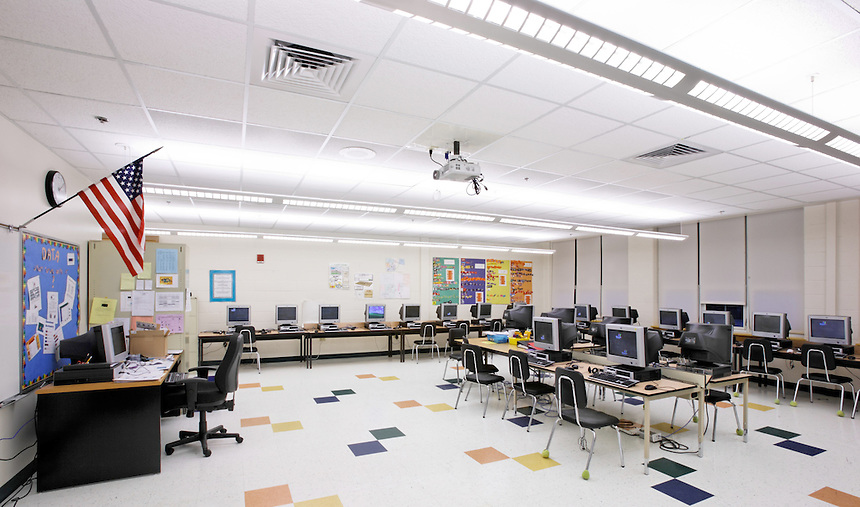 Computer classroom with suspended digital projector, computer stations and geometric tile floor.