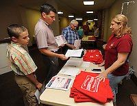 NWA Democrat-Gazette/ANDY SHUPE<br /> John Riordan (left) and his nephew Zack Riordan, both of Rudy, collect information Tuesday, Aug. 11, 2015, with help from volunteer Kimmie Bogan (right) of Lowell during a rally in opposition of the city of Fayetteville's proposed Uniform Civil Rights Protection ordinance at University Baptist Church in Fayetteville. Protect Fayetteville organized the rally as a &ldquo;rally against religious persecution&quot; ahead of the Sept. 8 vote to approve the ordinance.