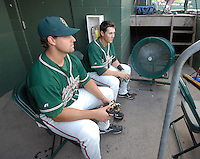 Ryan Keedy (41), left, and Justin Bass (14) of the Greensboro Grasshoppers cool off in front of the fan in the team's dugout on a day in the high 90s before a game against the Greenville Drive on June 14, 2010, at Fluor Field at the West End in Greenville, S.C. Photo by: Tom Priddy/Four Seam Images