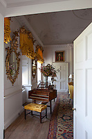 View through an open door into the parlour, its windows dressed with golden yellow curtains, ruched under carved and gilded pelmets