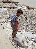 Boy sifting through rubbish on the street, Hadibu, Socotra, Yemen