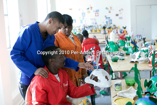 JOHANNESBURG, SOUTH AFRICA - MAY 10: An unidentified artist teaches a fellow artists how to paint a Makarapa helmet on May 10, 2010, in Alfred Baloyi's studio in Wynberg, north of Johannesburg, South Africa. Mr. Baloyi, and a diehard Kaizer Chiefs soccer fan, started to make these hats in 1979. Initially he asked a friend who worked at a construction site for a helmet, as he wanted to protect himself from missiles at games. He later started to paint it, and later started to make this different figures hand cut out from the helmet. During the years he has made many different artistic hats that are on display in his studio in a shack in Primrose, Johannesburg. He later gave up his job as a washer of busses. From his small workshop in a squatter camp in Primrose south east of Johannesburg he recently made partner with an investor and have a brand new factory with about fifty people employed to make the hats. (Photo by Per-Anders Pettersson/Getty Images)