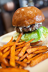 The Luxe Burger smothered in burrata on a brioche bun with sweet potato fries at FIGOLY Restaurant at Luxe City Center in Downtown Los Angeles, CA