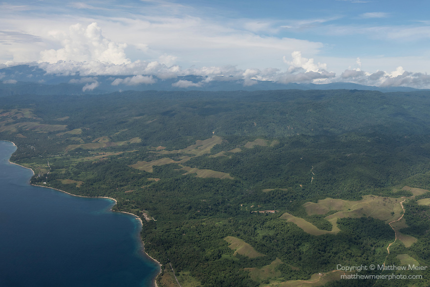 Guadalcanal, Solomon Islands; an aerial view of the countryside near the capital of Honiara, on Guadalcanal Island, with white puffy clouds overhead