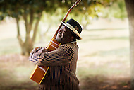An african-american blues musician closes his eyes and hugs his guitar.