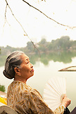 VIETNAM, Hanoi, portrait of a woman with a fan by Hoan Kiem Lake