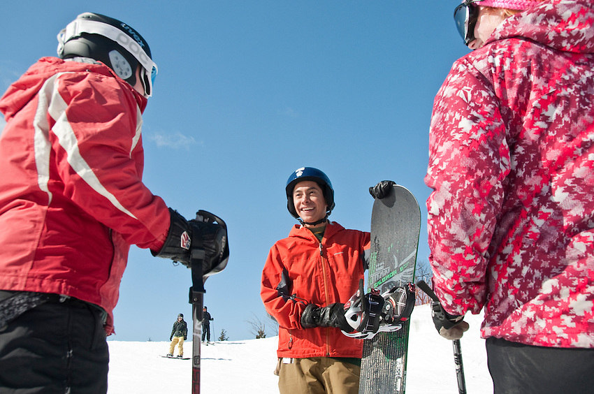 Skiers and snowboarders visit before a run at Marquette Mountain ski area in Marquette Michigan.