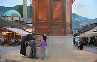 Woman and children drinking at the Sebilj, a public fountain in Ottoman style made from wood on a stone base, built 1891, in Bascarsija Square, Sarajevo, Bosnia and Herzegovina. Behind is the 16th century Gazi Husrev-beg Mosque. The square is also called Pigeon Square as people sit in the cafes drinking coffee and feeding the many pigeons which congregate here. The city was founded by the Ottomans in 1461. Picture by Manuel Cohen