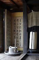 On the veranda immediately beyond the living room an ancient millstone is placed before a folded screen decorated with Japanese calligraphy