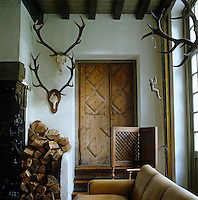 In the corner of the living room a rustic wooden door is framed by sets of antlers