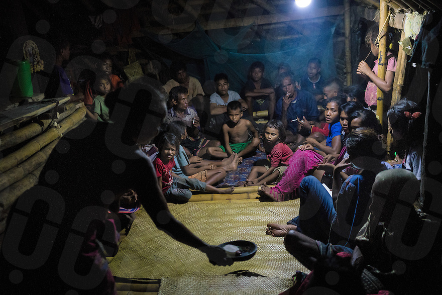"""March 25, 2016 - Wainyapu (Indonesia). Villagers gather inside the house of the """"Rato"""" - the traditional priest leader - singing a traditional song to call the """"Nyale"""" -  a sea worm that normally appears on the shore on Pasola day. The number of nyale collected is believed to be a sign of the richness of the farmers' next harvest season. © Thomas Cristofoletti / Ruom"""