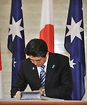 AUSTRALIA, Canberra : Japanese Prime Minister Shinzo Abe signs the visitors book at Parliament House in Canberra on July 8, 2014. Defence ties are set to take centre stage when Australia plays host to Japanese Prime Minister Shinzo Abe this week, as the two countries look set to strengthen their relationship through annual leaders' meetings. AFP PHOTO / Mark GRAHAM