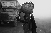 A woman standing with a busket of coal on her head. Unemployed women and children collect coal that falls from the loaded trucks to sell them in the illegal coal market. Arindam Mukherjee