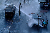 Santiago, Chile<br /> October 1988<br /> <br /> Police disperse demonstrators who demand the immediate removal of General Pinochet with powerful water cannons.<br /> <br /> In October 1988, General Augusto Pinochet ordered a plebiscite vote asking Chilean citizens whether he should continue in office. It produced a decisive &quot;no&quot; vote and the following year he lost the first presidential election in 19 years. However, under a constitution crafted by his advisors, he remained as army commander until 1998. Pinochet continued to wield enormous power until his arrest in London on human rights charges in October 1998.