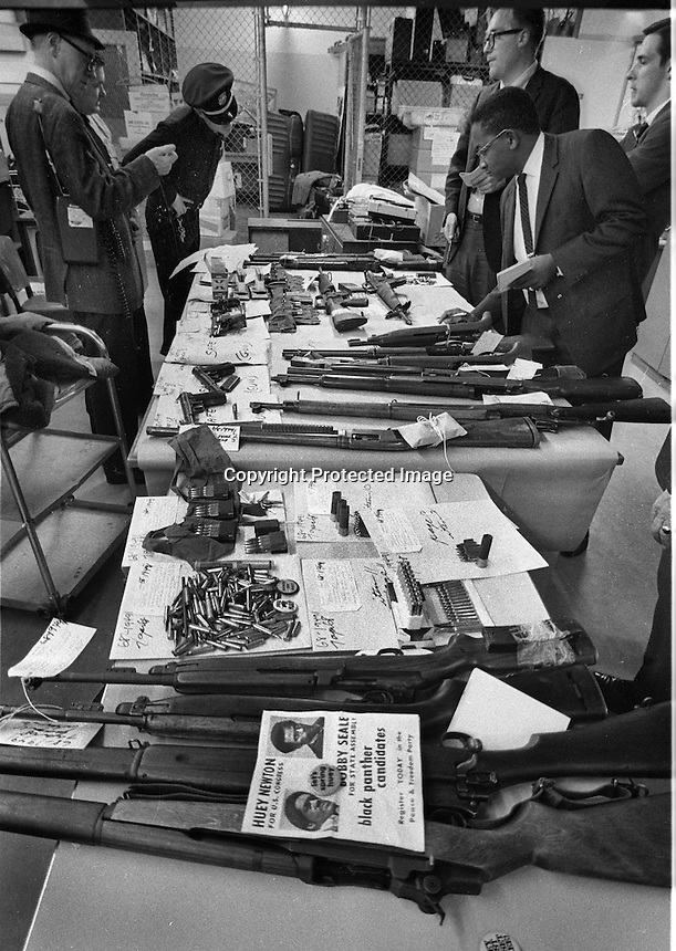 Oakland Police show news reporters the recovered Black Panther guns at the police station property room. (1968 photo by Ron Riesterer)