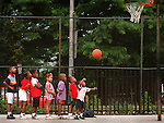 BALTIMORE, MD, JUNE 19--Damien Coleman, 3, is encouraged by his friends to shoot hoops at Margaret Brent Elementary in the 2500 blockof St. Paul this morning, but his shot came up a bit short.  The daycare group from Waverly was on a field trip to downtown Baltimore and decided to stop at the playground.  (Sun staff/Larry C. Price).