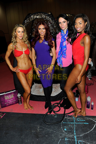 Amy Childs.Amy Childs photocall before (Failed)  Guinness World Record Attempt of the most people being spray tanned at the same time at the Professional Beauty Show, Excel, London, England..February 25th, 2013.full length purple dress red bikini pink top blue scarf black tights.CAP/CJ.©Chris Joseph/Capital Pictures.