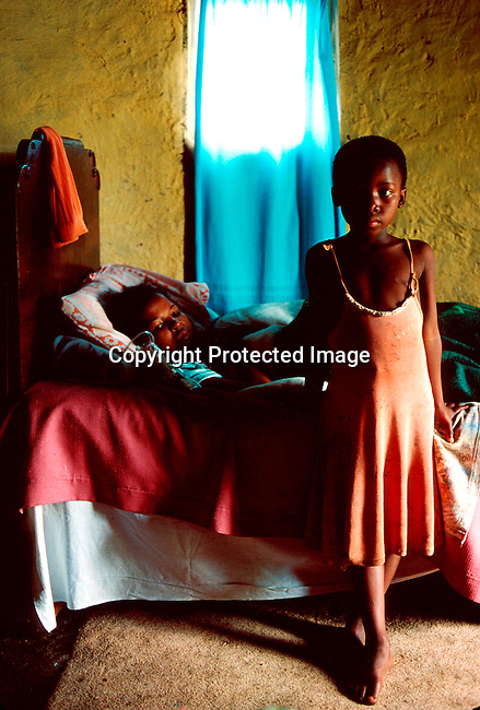 disiaids00259  Social Issues, Aids, Health. A young girl at her mother's side in Izingolweni, a rural village in Southern Natal in South Africa. The mother is dying of an Aids related disease.Her only daughter will be taken care of by grand parents; young girl standing; sick woman in bed; health..©Per-Anders Pettersson/iAfrika Photos