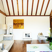 The golden colours of a single painting in the otherwise white living room pick up the tones in the wood of the floorboards and beams