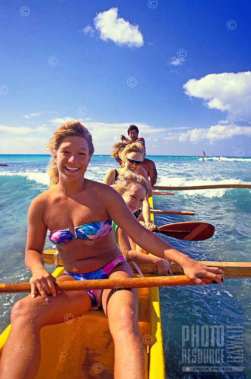 Water and sun drenched vacationers smile with delight on their yellow outrigger canoe gliding on the beautiful blue waters off Waikiki Beach.