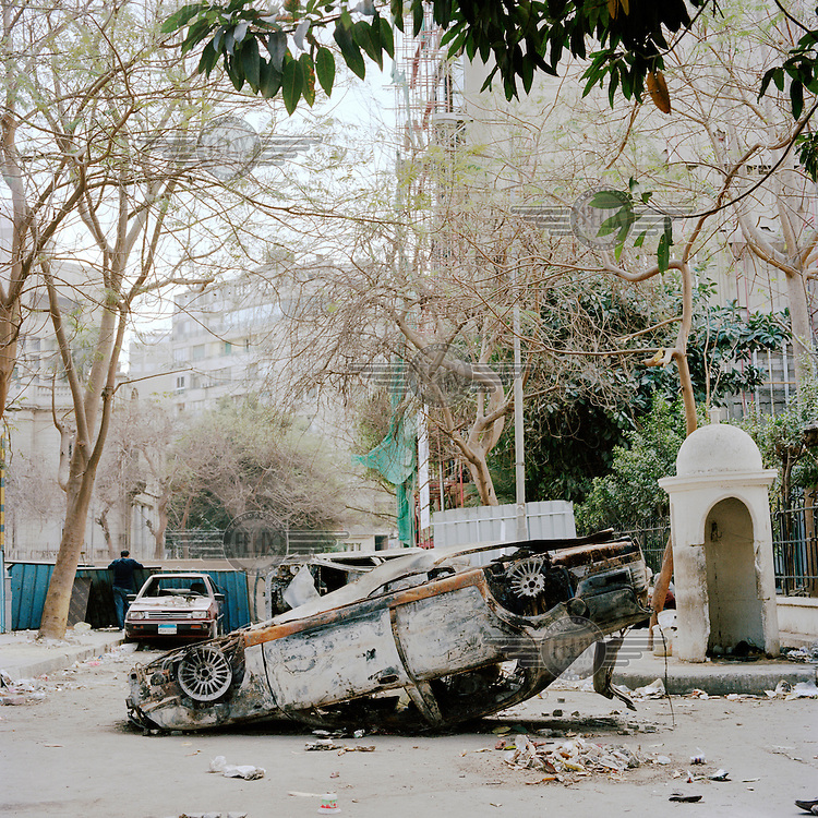 A burnt out car lies upside down in the street outside the Omar Makram mosque in Tahrir Square. 25 January 2011 saw the beginning of a nationwide 18 day protest movement that eventually ended the 30-year rule of Hosni Mubarak and his National Democratic Party. .