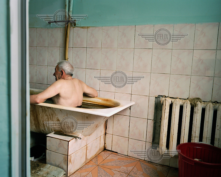 Muzafar, a patient at the Naftalan Sanatorium. Each session, patients bathe for ten minutes in a tub of crude oil. The oil is heated to 37 degrees for optimum effectiveness.