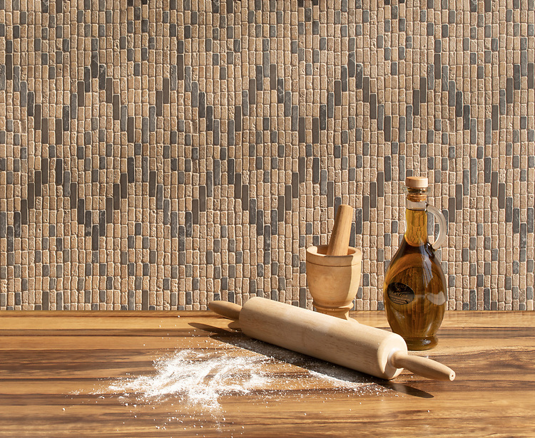 Dhurrie, a hand-cut stone mosaic, shown in tumbled Travertine Noce and Cavern, is part of the Tissé ® collection designed by Paul Schatz for New Ravenna.