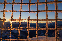 The sun sets over the Kenai Mountins, Turnagain Arm and Cook Inlet, framed by metal netting between hand rails at Alyeska Resort.