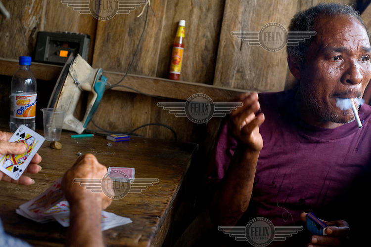 A tailor smokes as he plays a game of cards in the city of Borbon, a small community on the Cayapas River.