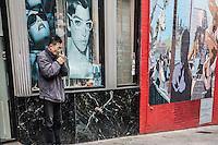 Uomo di origine cinese si accende una sigaretta davanti a un negozio di occhiali con pubblicit&agrave; di Prada<br /> Man of Chinese origin lights a cigarette in front of a shop of glasses with advertising Prada