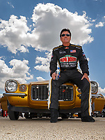 Jul 8, 2017; Joliet, IL, USA; Papa Johns Pizza founder John Schnatter sits on the hood of his gold Camaro prior to taking on NHRA top fuel driver Leah Pritchett (not pictured) in a Charity Challenge race to raise funds and awareness for Infinite Hero Foundation during qualifying for the Route 66 Nationals at Route 66 Raceway. Mandatory Credit: Mark J. Rebilas-USA TODAY Sports