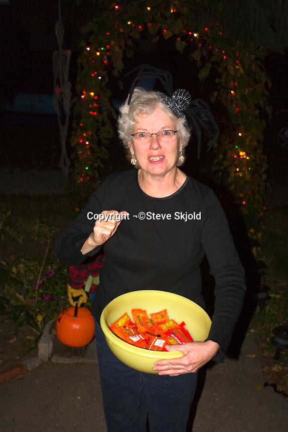 Neighbor age 63 in Halloween spider costume offering Reeses Pieces tricks or treats.  St Paul Minnesota USA