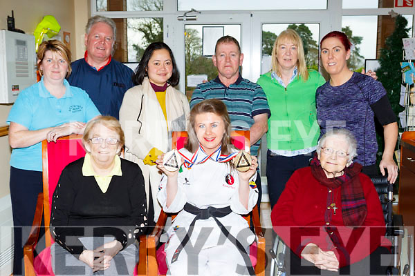 Katie O'Neill Mastergeeha brought the two gold medals she won at the Karate Worldwide Championships in Birmingham England to show her colleagues and residents of Our Lady Of Lourdes Nursing home Kilcummin last Friday front row l-r:  Kathleen O'Shea, Katie O'Neill, Sr Aysias Courtney. Back row: Martina O'Riordan, Patrick Doody, Hanfev Mouabosa, Dan Horan, Irene Coleman, and Margaret O'Donoghue