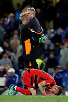 Huddersfield Town's Assistant Head Coach, Christoph Buhler and goalkeeper, Jonas Lossl celebrate at the final whistle as Florent Hadergjonaj emotionally puts his head against the Stamford Bridge grass during Chelsea vs Huddersfield Town, Premier League Football at Stamford Bridge on 9th May 2018