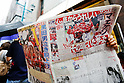 A Hiroshima Carp baseball team fan reads a newspaper while lines up outside Hiroshima Brand Shop TAU in Ginza on September 11, 2016, Tokyo, Japan. Hundreds of Carps fans lined up from early morning outside Hiroshima Brand Shop TAU to buy victory t-shirts after Hiroshima baseball team got its first Central League title in 25 years after beating the Yomiuri Giants 6-4 on Saturday, September 10. (Photo by Rodrigo Reyes Marin/AFLO)