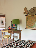 A simple wooden side table in the guest bedroom with a forest green lamp and brightly coloured painting