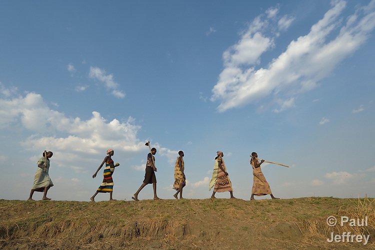After working together in a community garden, women walk home on April 12, 2017, atop a dyke they constructed to control flooding around Dong Boma, a Dinka village in South Sudan's Jonglei State. Most of the women's families recently returned home after being displaced by rebel soldiers in December, 2013, and they face serious challenges in rebuilding their village while simultaneously coping with a drought which has devastated their cattle herds.<br /> <br /> The Lutheran World Federation, a member of the ACT Alliance, is helping villagers restart their lives with support for housing, livelihood, and food security.