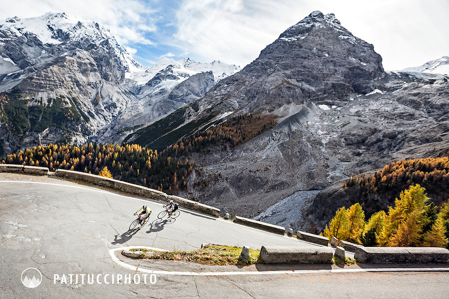 Road bikers riding uphill on the Passo Stelvio's east side on a sunny fall day, Italy
