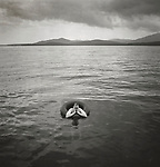 Scans of vintage black and white prints. Brendan Works meditating in inner tube on Moosehead Lake, ME. Negative file #99-082-D7. 1999.