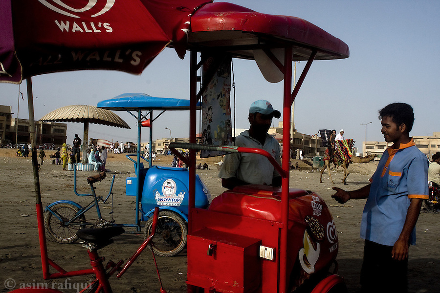 Ice cream vendors surround families enoying a day at the beach at Karachi's famous Clifton Beach waterfront.