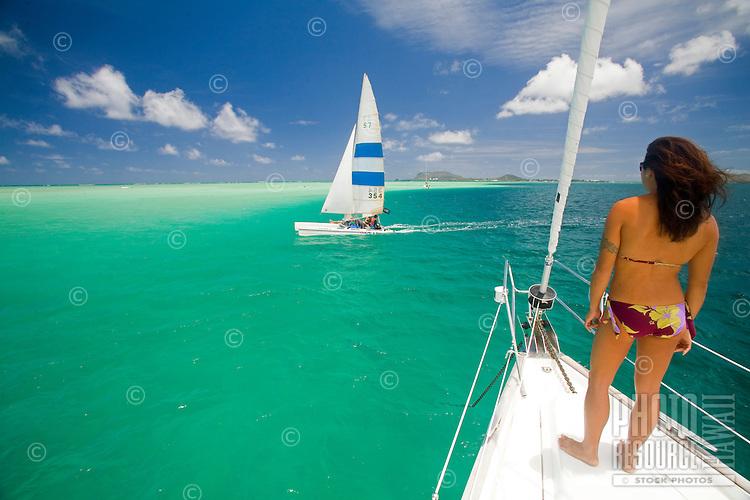Young girl in bikini on the bow of a sailboat watching a catamaran sailing in Kaneohe Bay, Oahu, Hawaii